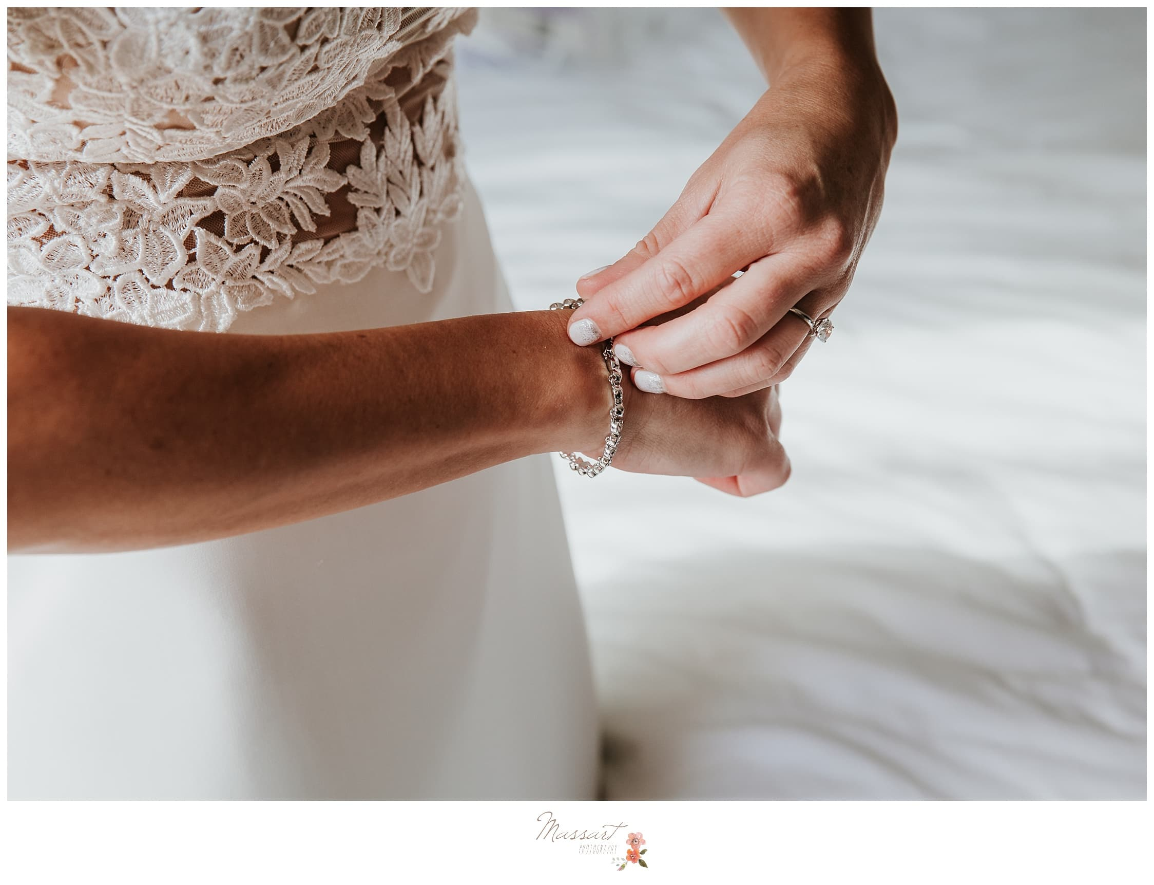 Bride puts on her bracelet for the wedding ceremony photographed by Massart Photography Rhode Island