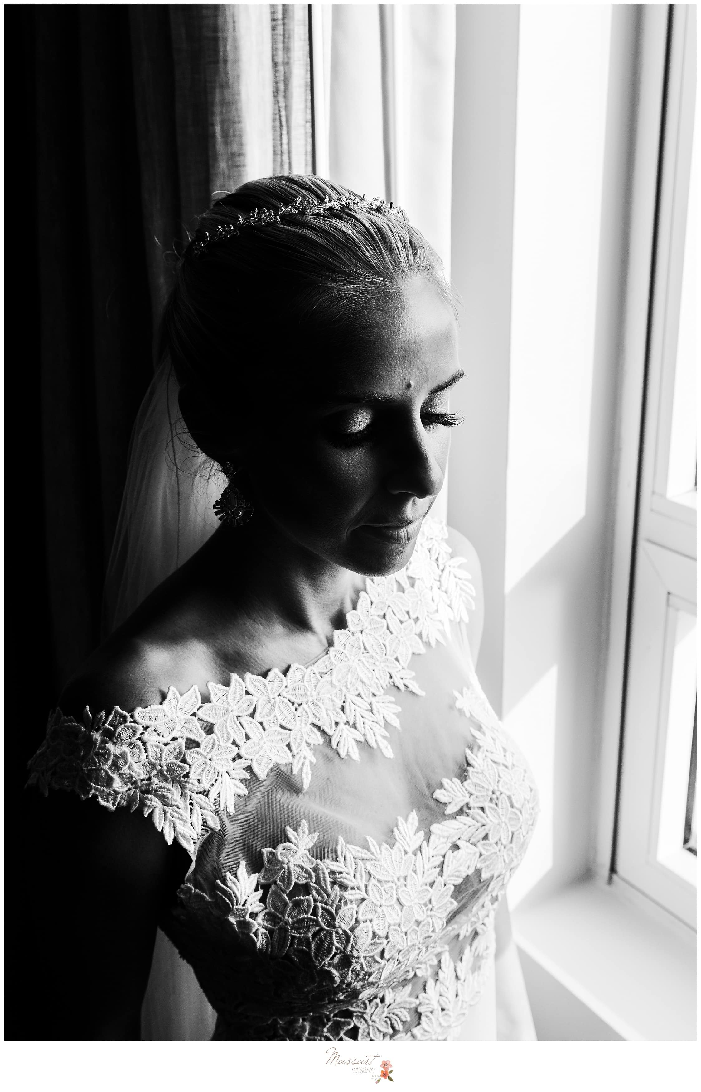 Black and white portrait of the bride dressed in her wedding gown by the window photographed by Massart Photography RI