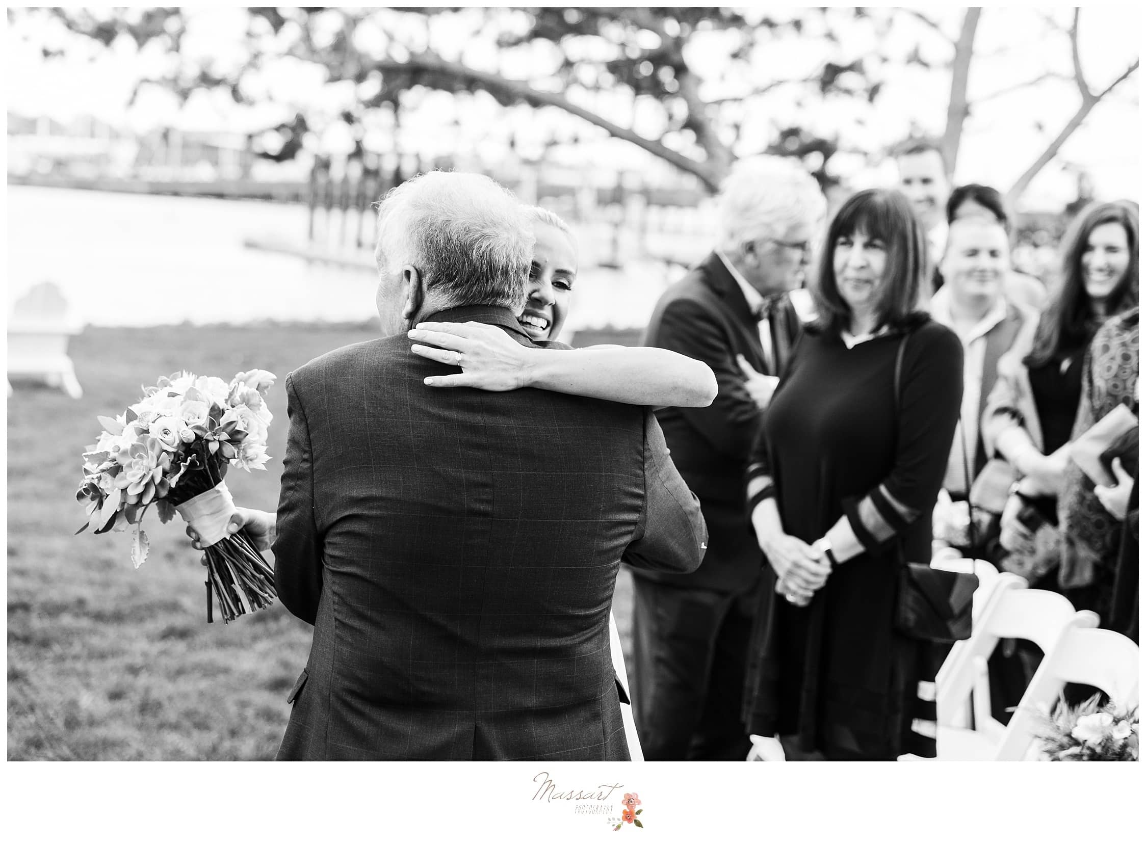 Bride and her father hug at the wedding ceremony photographed by Massart Photography Rhode Island
