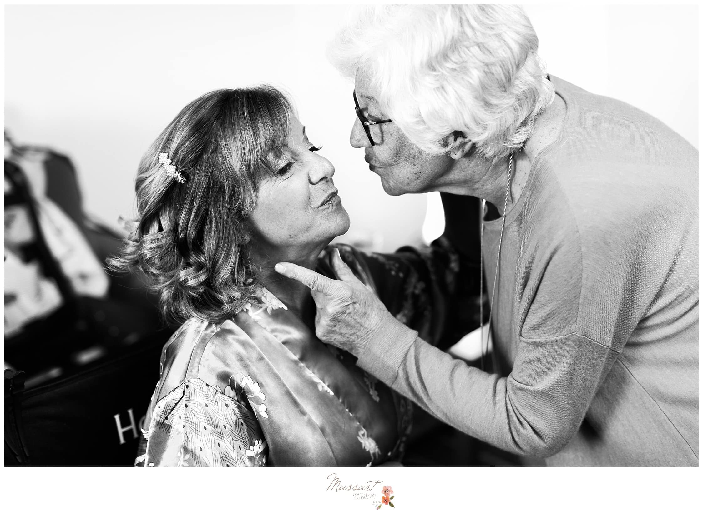 Bride's mother and grandmother share a kiss before the wedding ceremony photographed by Massart Photography RI