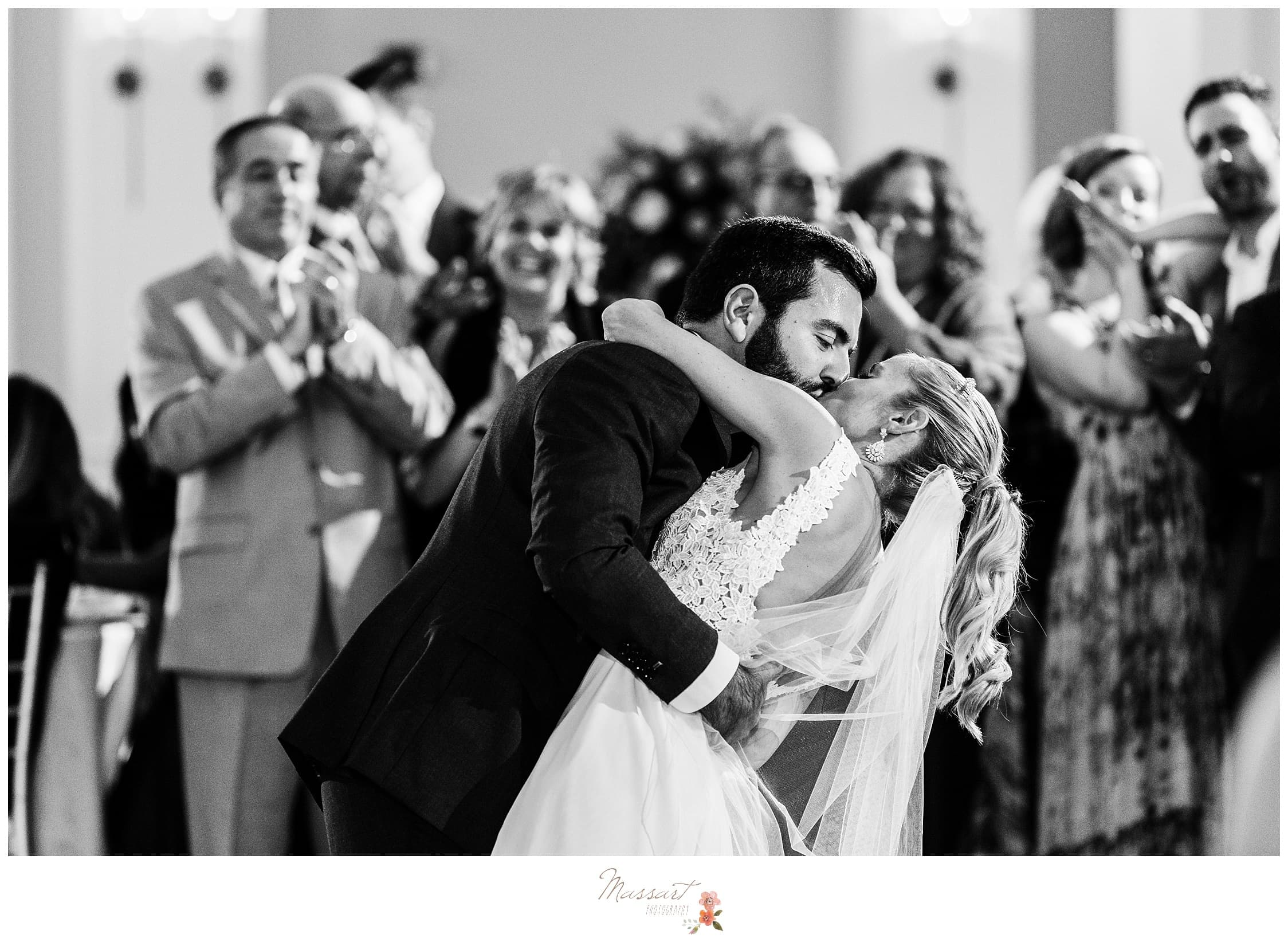 Black and white portrait of the bride and groom kissing during their first dance photographed by Massart Photography Rhode Island