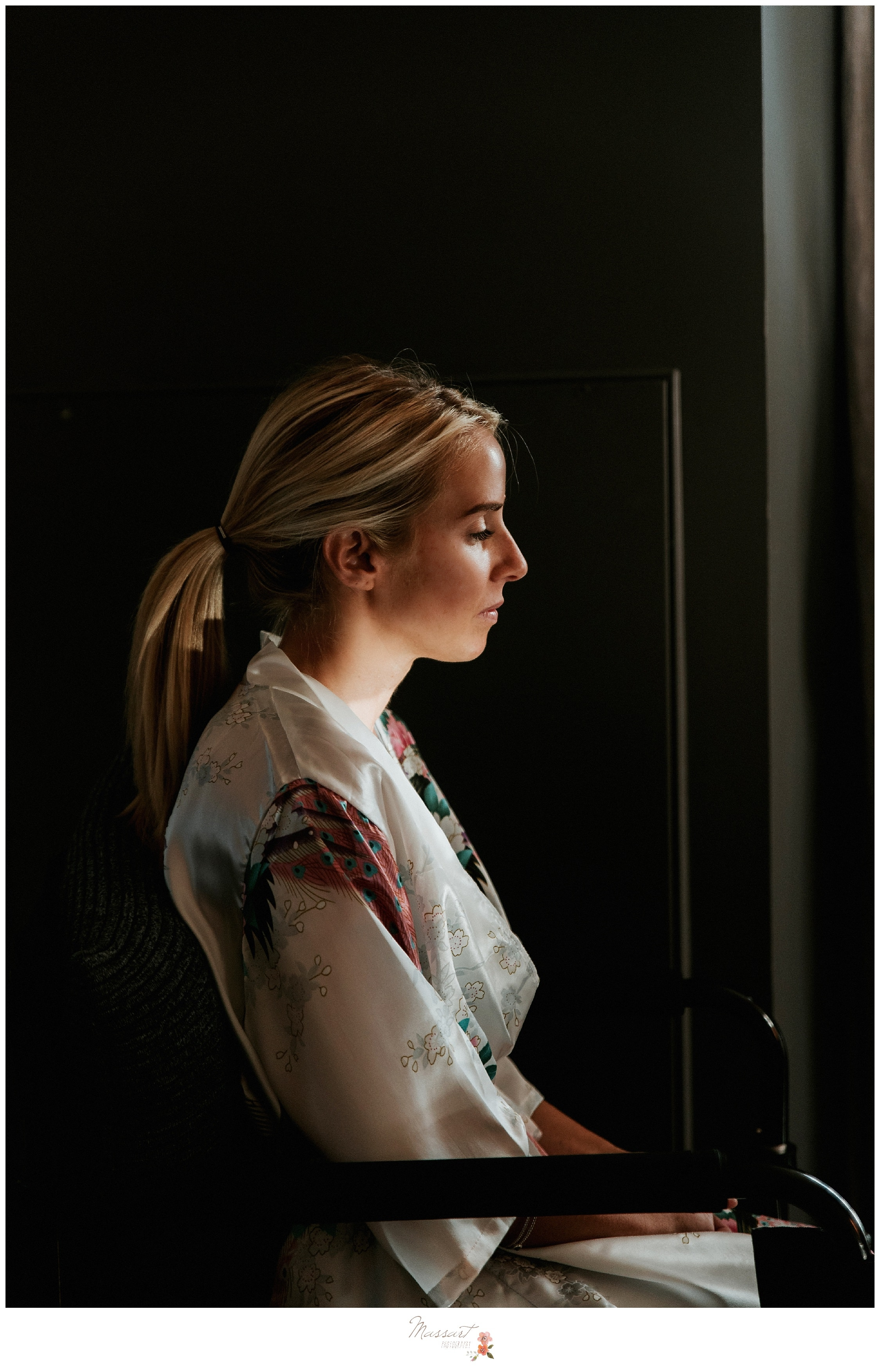 Bride looking out the window while getting ready for the wedding ceremony photographed by Massart Photography RI