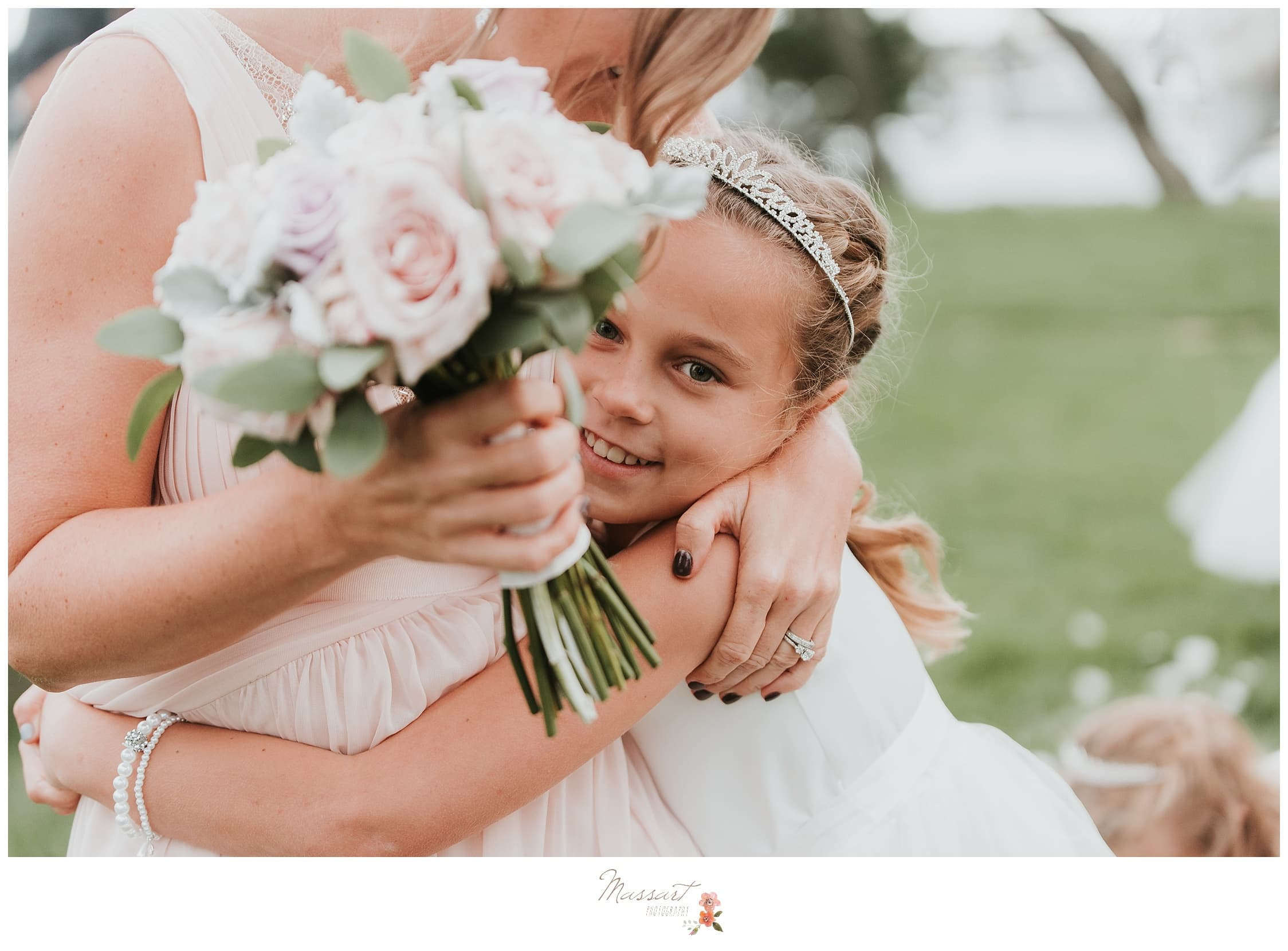 Flower girls hugs one of the bridesmaids photographed by Massart Photography Rhode Island