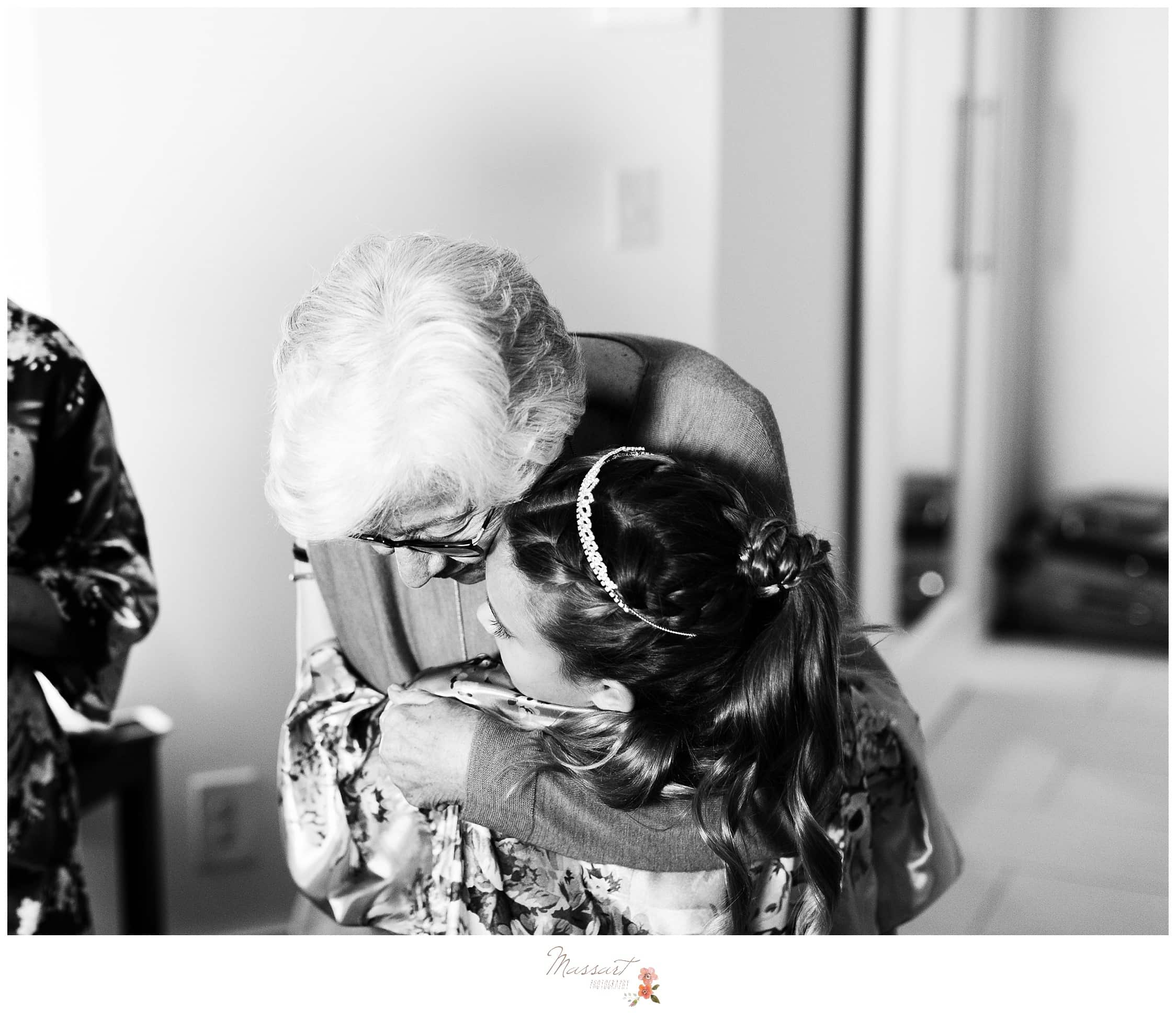 Grandma and the flower girl sharing hugs before the wedding ceremony photographed by Massart Photography Rhode Island