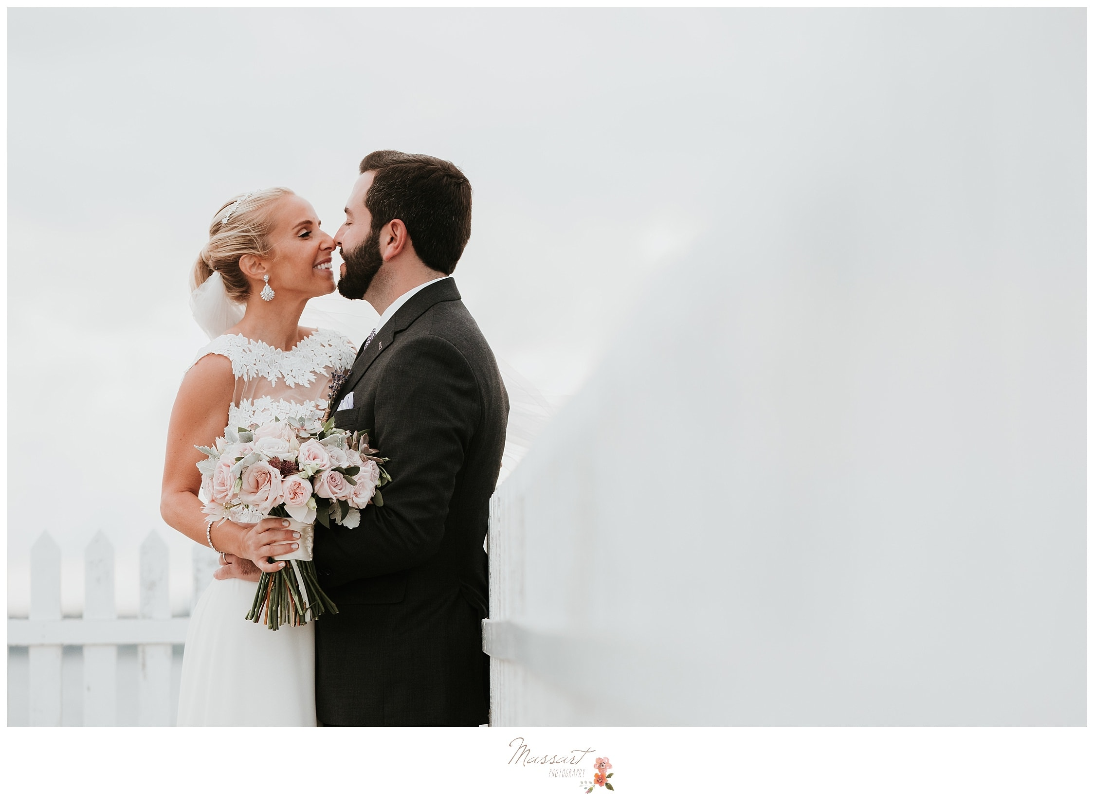 Romantic portrait of the bride and groom with her veil floating in the wind photographed by Massart Photography Rhode Island