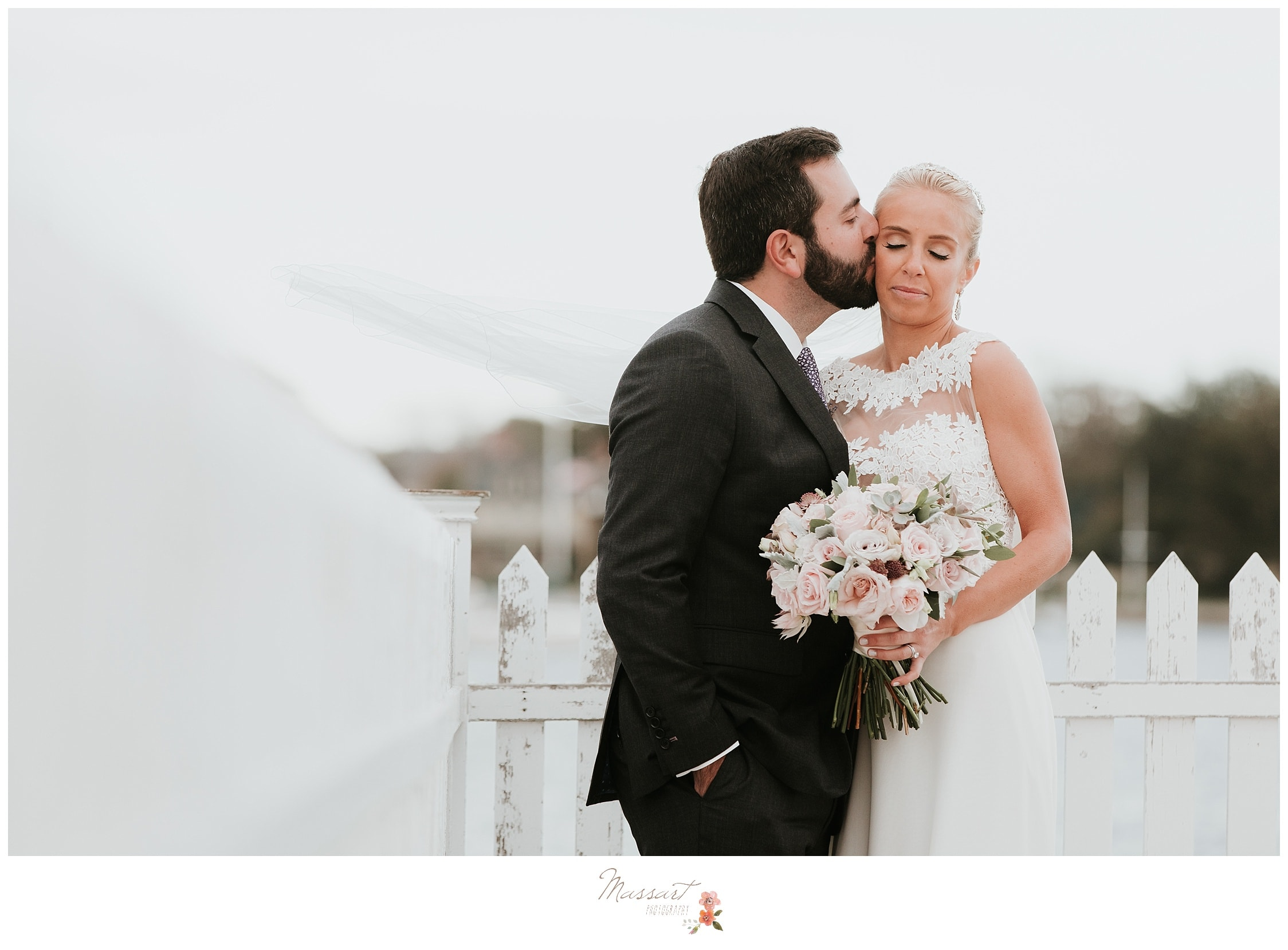 Groom kisses his bride on the cheek photographed by Massart Photography RI