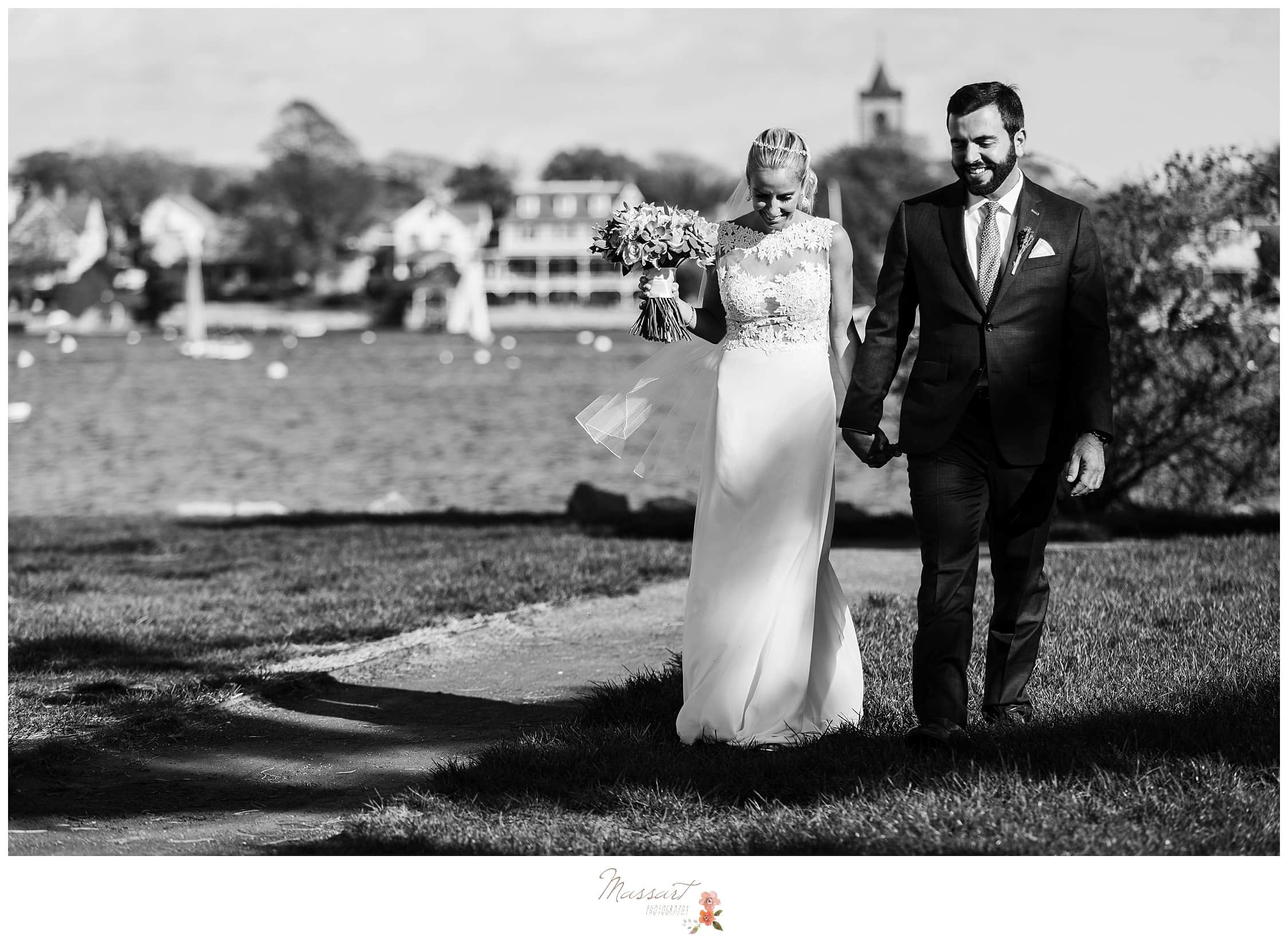 Black and white portrait of the bride and groom walking along Goat Island in Newport, RI photographed by Massart Photography Rhode Island