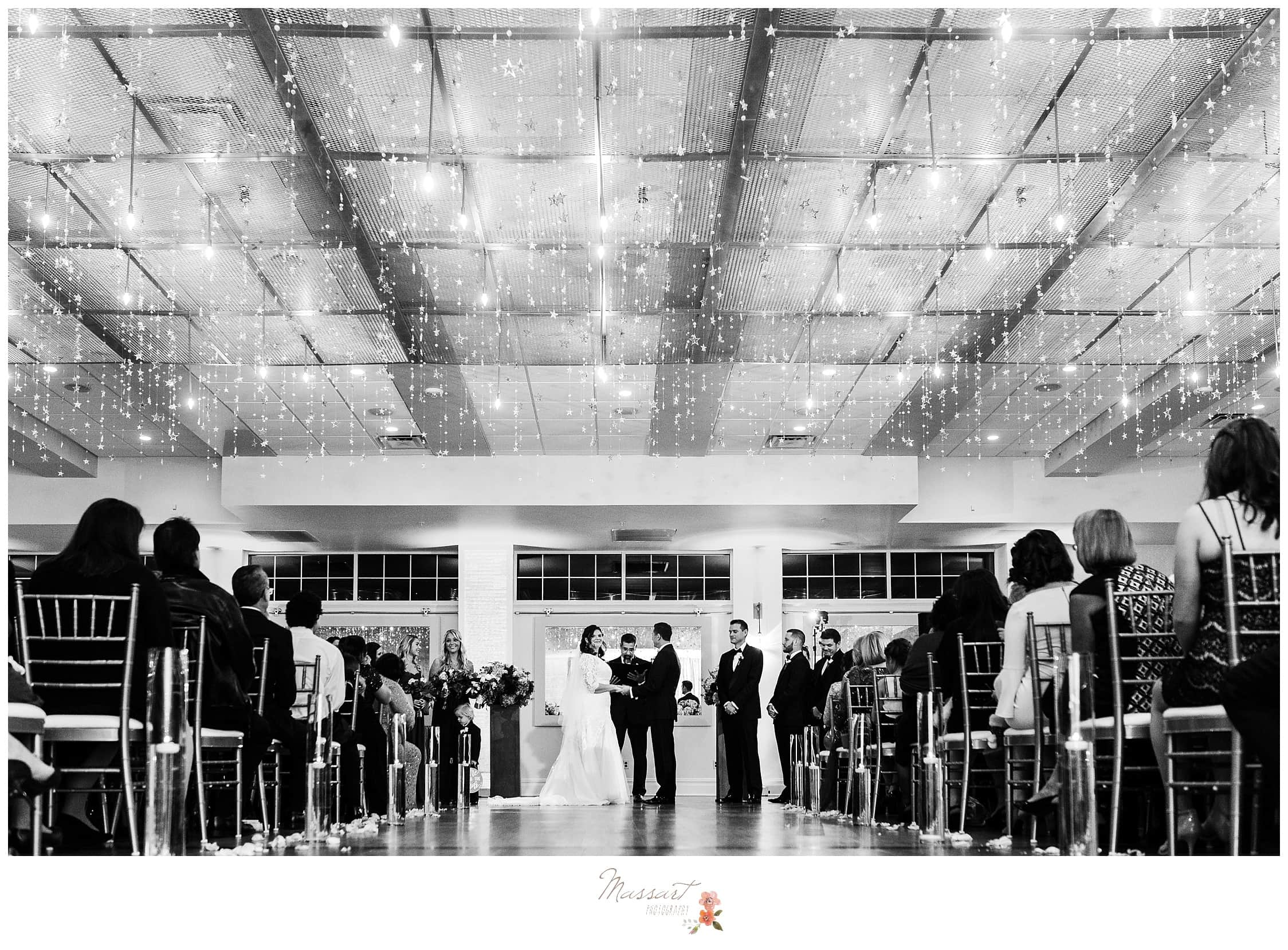 Dramatic picture of the wedding ceremony in the ballroom at the atlantic resort captured by massart photography