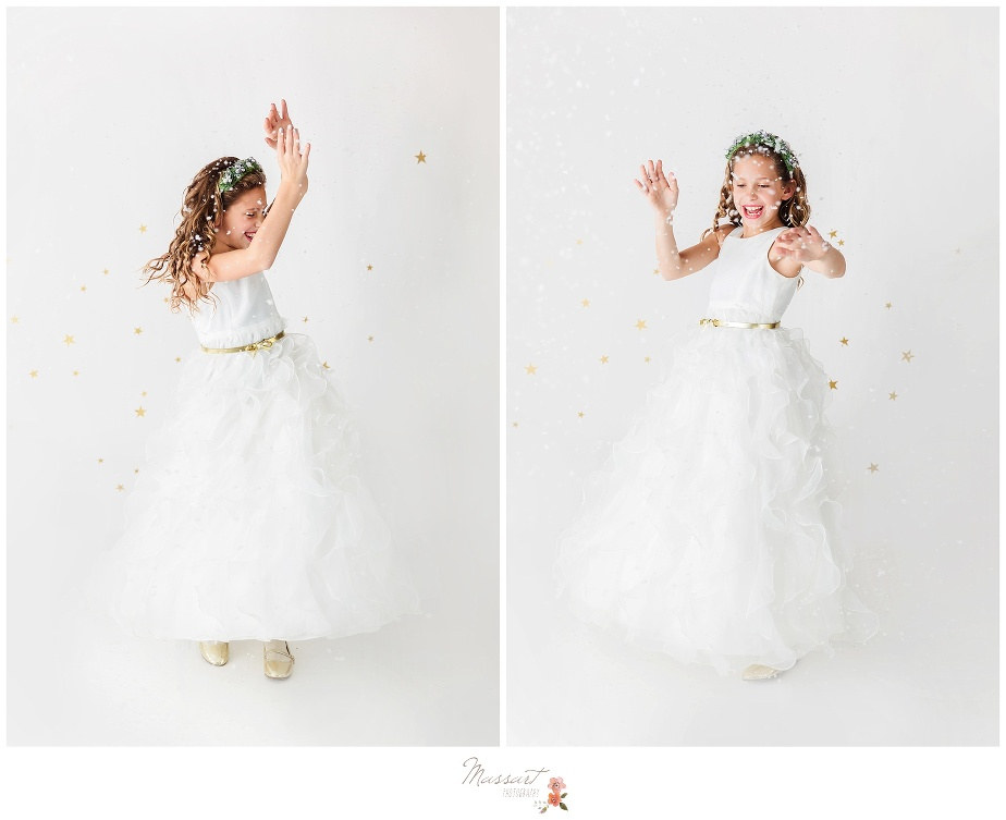 Little girl wearing white dress twirls in the fake snow during holiday portrait session photographed by Massart Photography Rhode Island