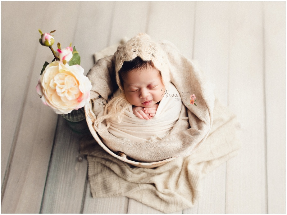 Baby photo by Massart Photographers in their warwick, Rhode Island photography studio. Also servicing CT and MA. Baby in bucket using soft tones.