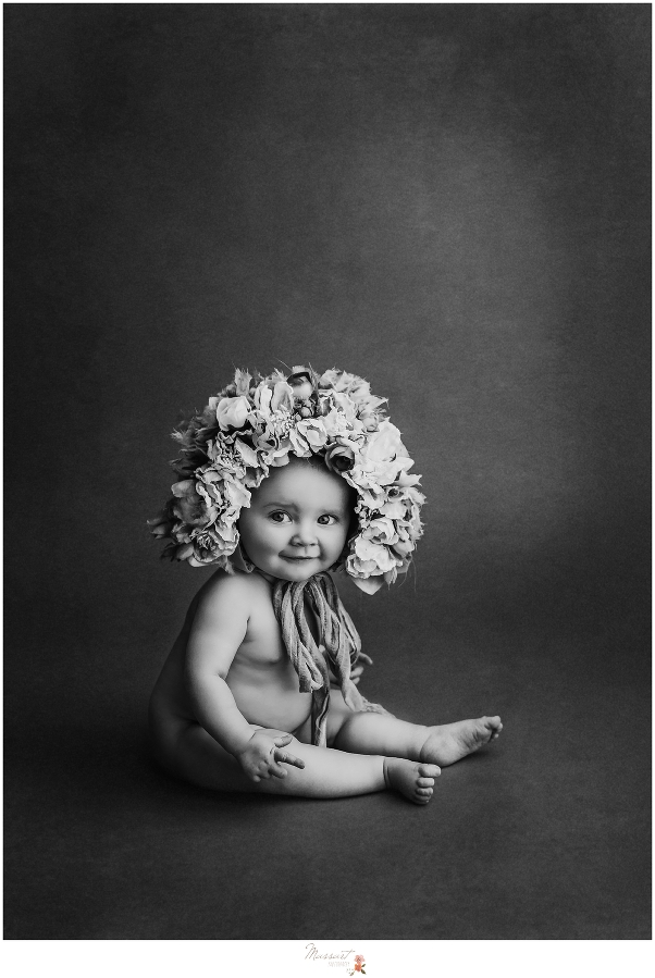 Dramatic black and white portrait of a baby during a studio session by Massart Photographers who service RI, CT and MA. Inspired by Anne Geddes.