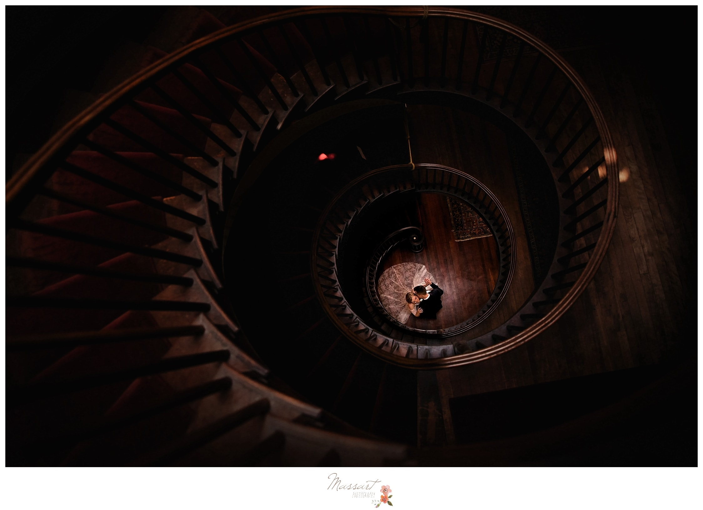A dramatic staircase wedding portrait of the bride and groom at Linden Place in Bristol, Rhode Island. Captured by Massart Photographers from a newborn, family and wedding photo studio in RI