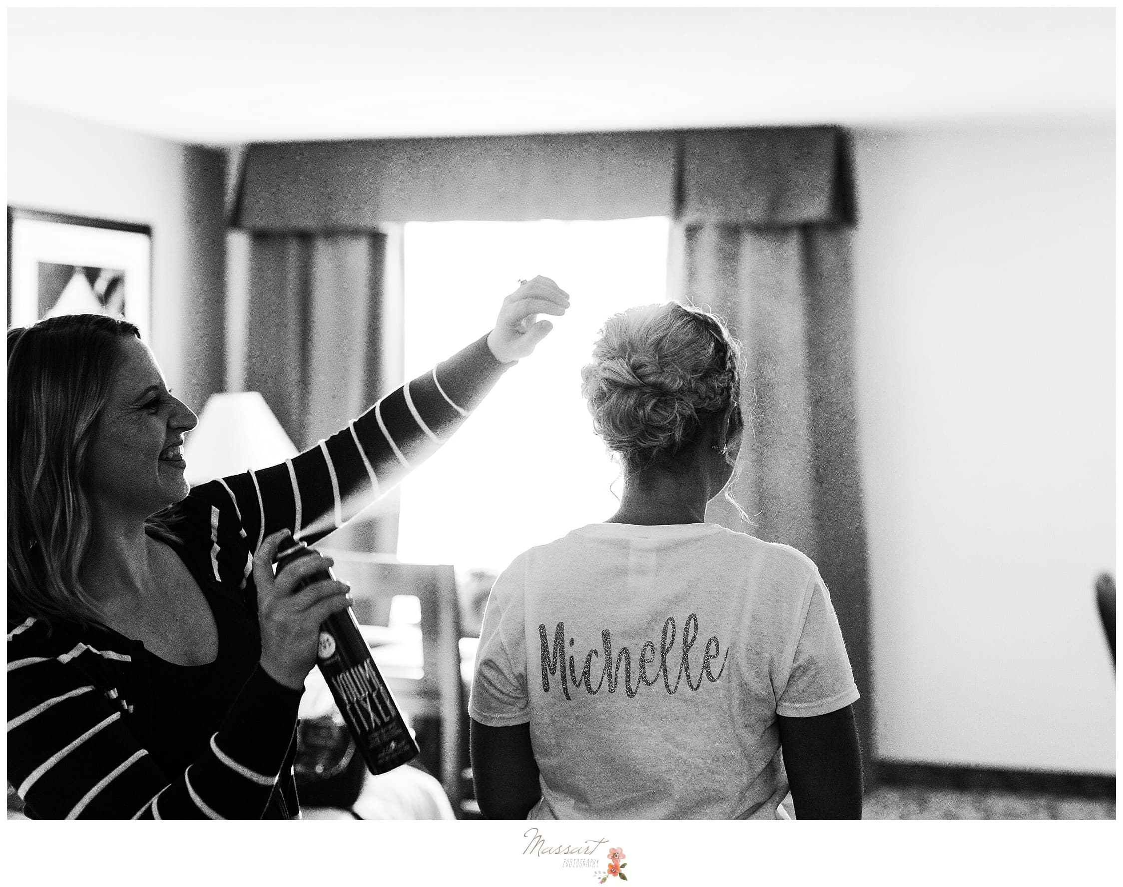 Bridesmaid getting hair done while prepping for Harbor Lights wedding in RI photographed by Massart Photography.