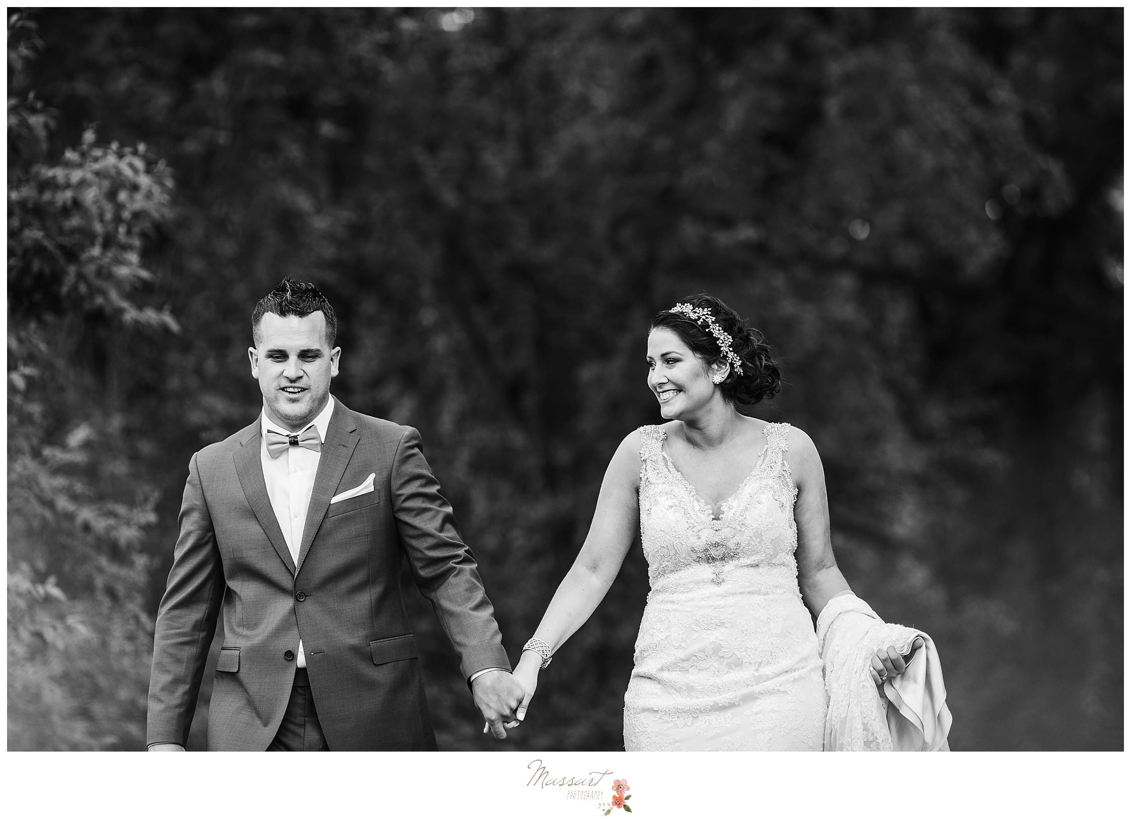 Bride and groom holding hands and walking during portraits at summer wedding in RI photographed by Massart Photography, who specialize in east coast weddings.