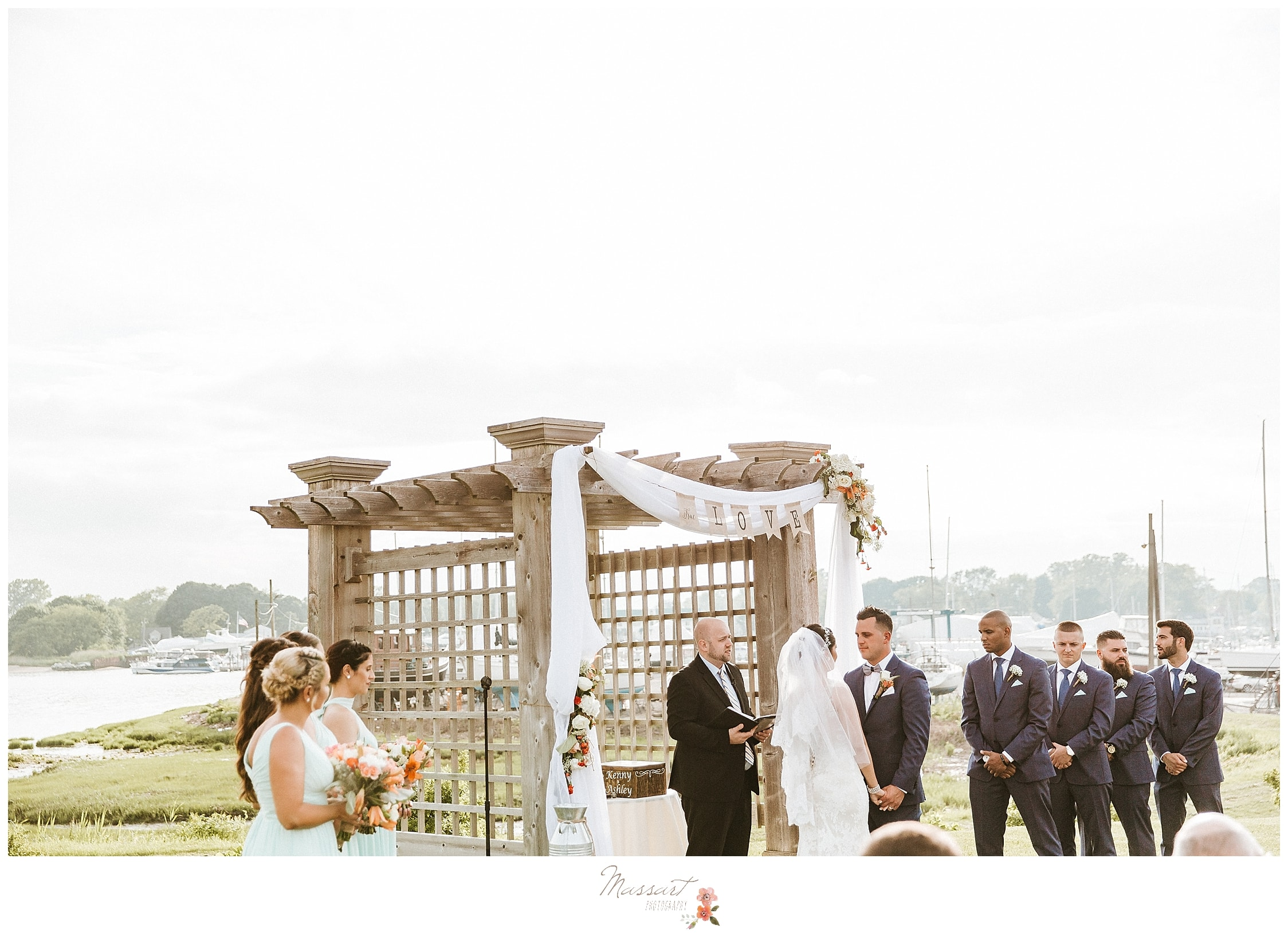 Outdoor ceremony with an arbor at Harbor Lights in RI photographed by wedding photographers Massart Photography.