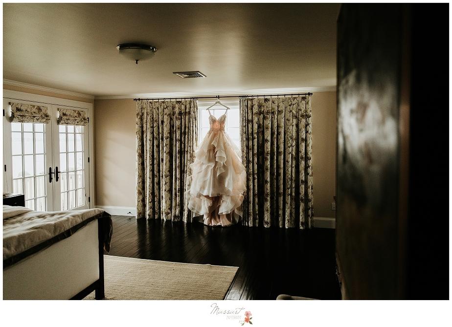 Wedding dress hanging in window captured by Stonington CT wedding photographers Massart Photography