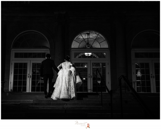 bride and groom walking up Aldrich Mansion stairs to return to their wedding reception in RI
