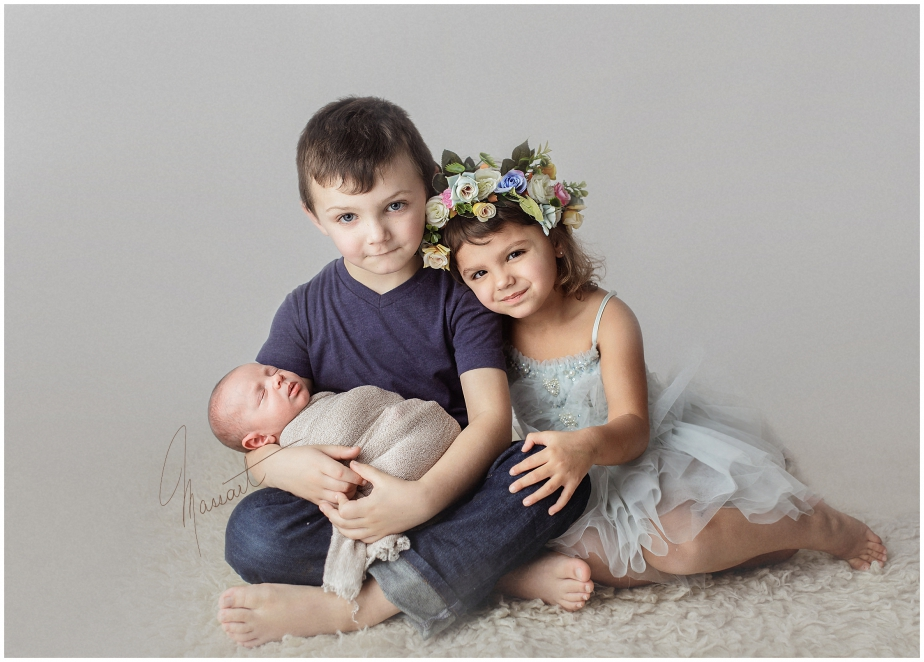 A baby and siblings timeless image during a newborn session in Rhode Island