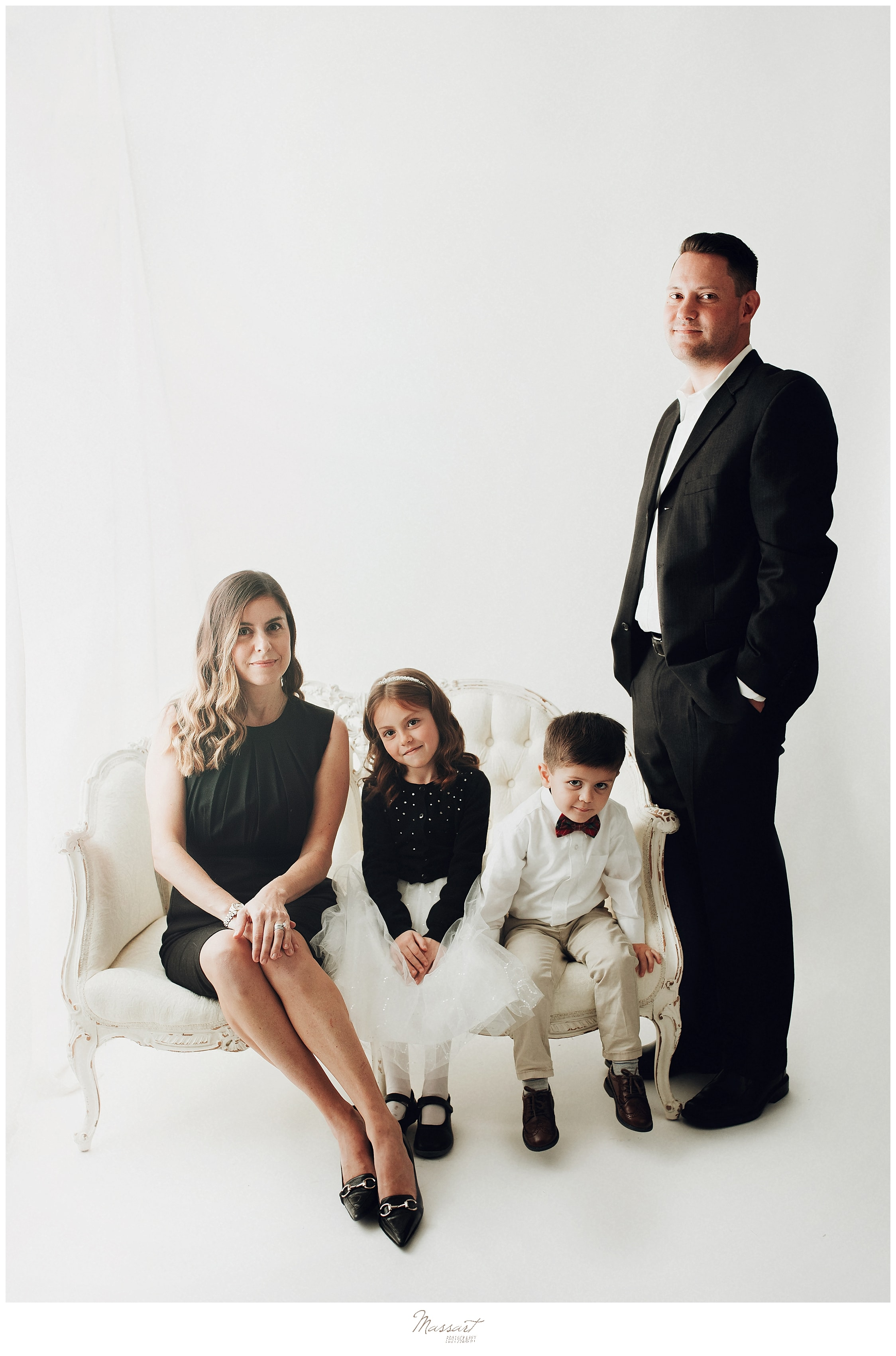 Family poses for a traditional timeless portrait at a Rhode Island photo studio during their family session