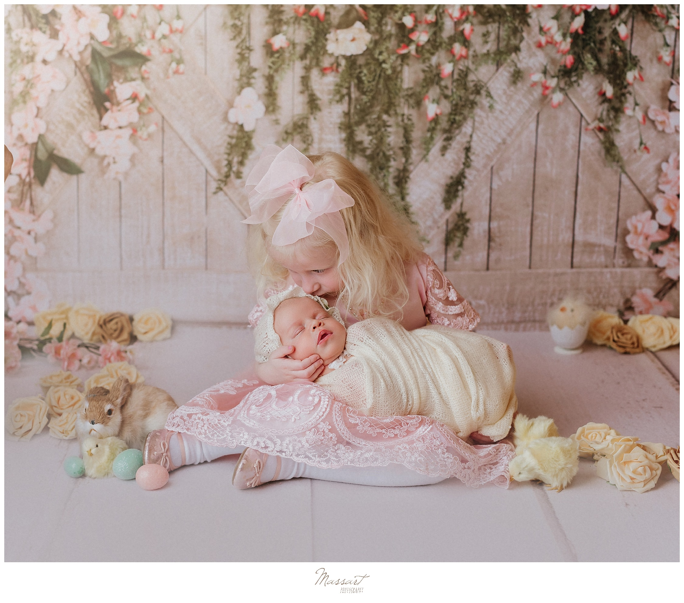 Easter mini sessions at Massart Photography; sister and baby newborn pose for a picture