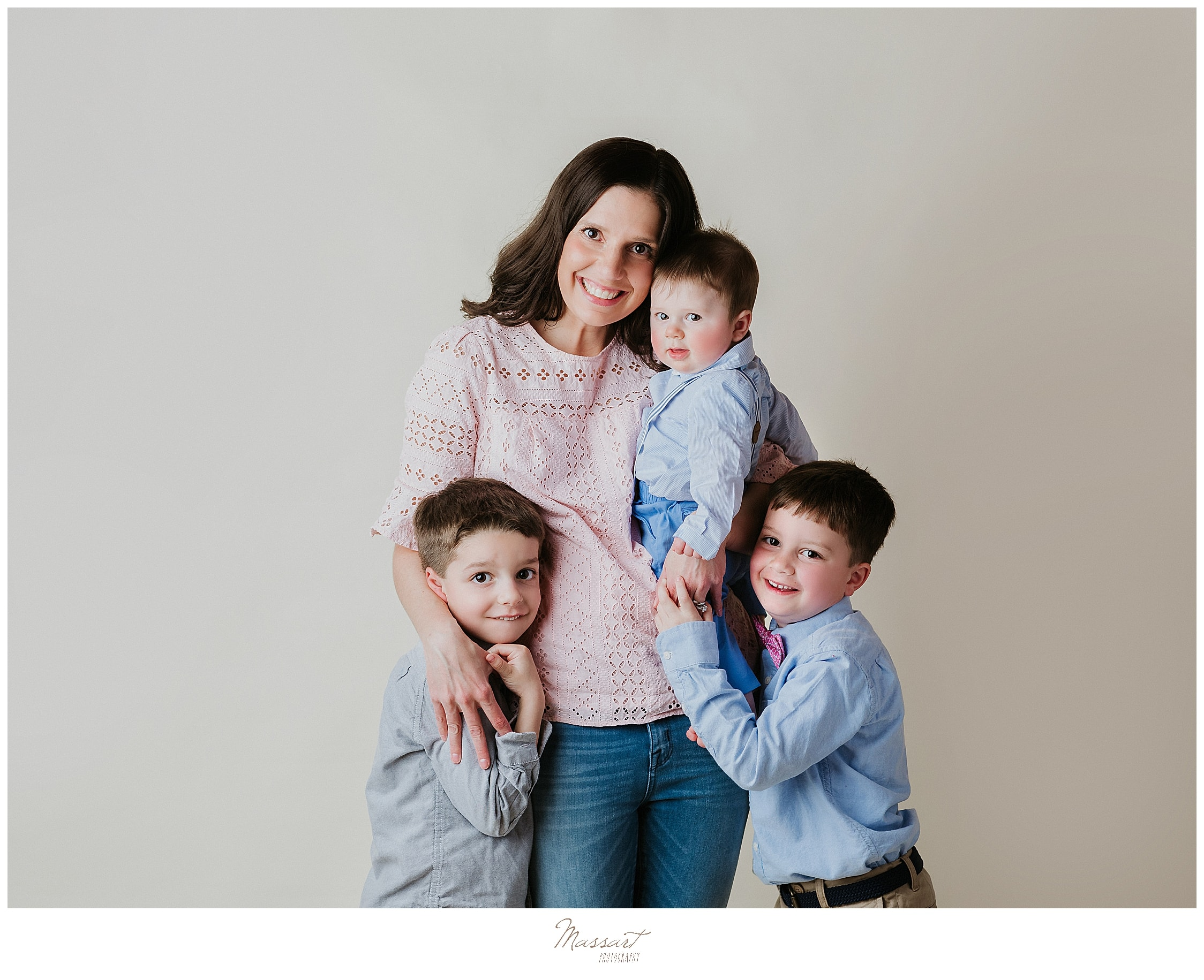 Mother poses with her sons for a family portrait at a Rhode Island photo studio