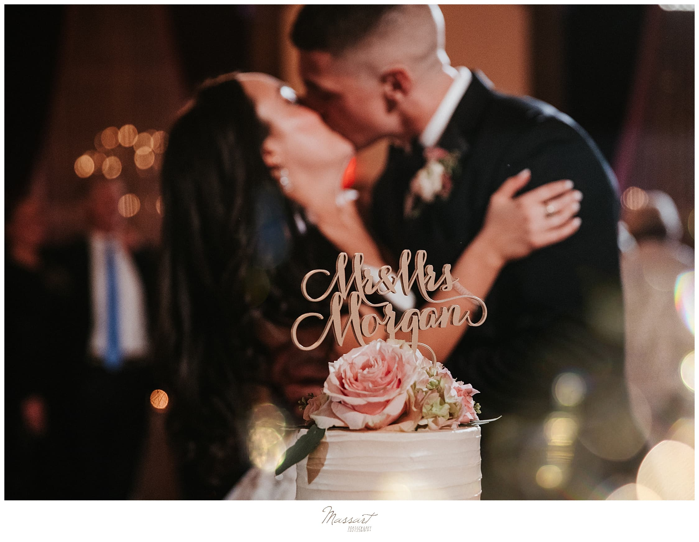 couple kisses by wedding cake photographed by wedding photographers Massart Photography