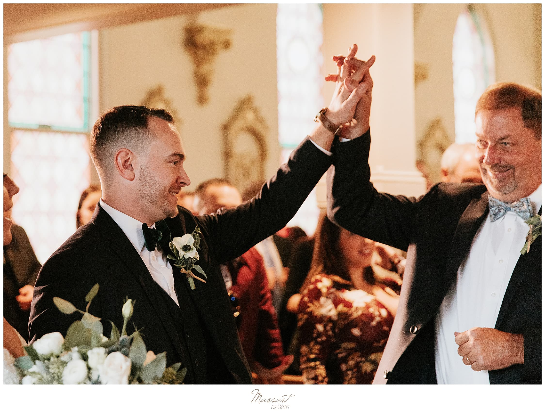 groom high fives groomsmen at ceremony photographed by Massart Photography