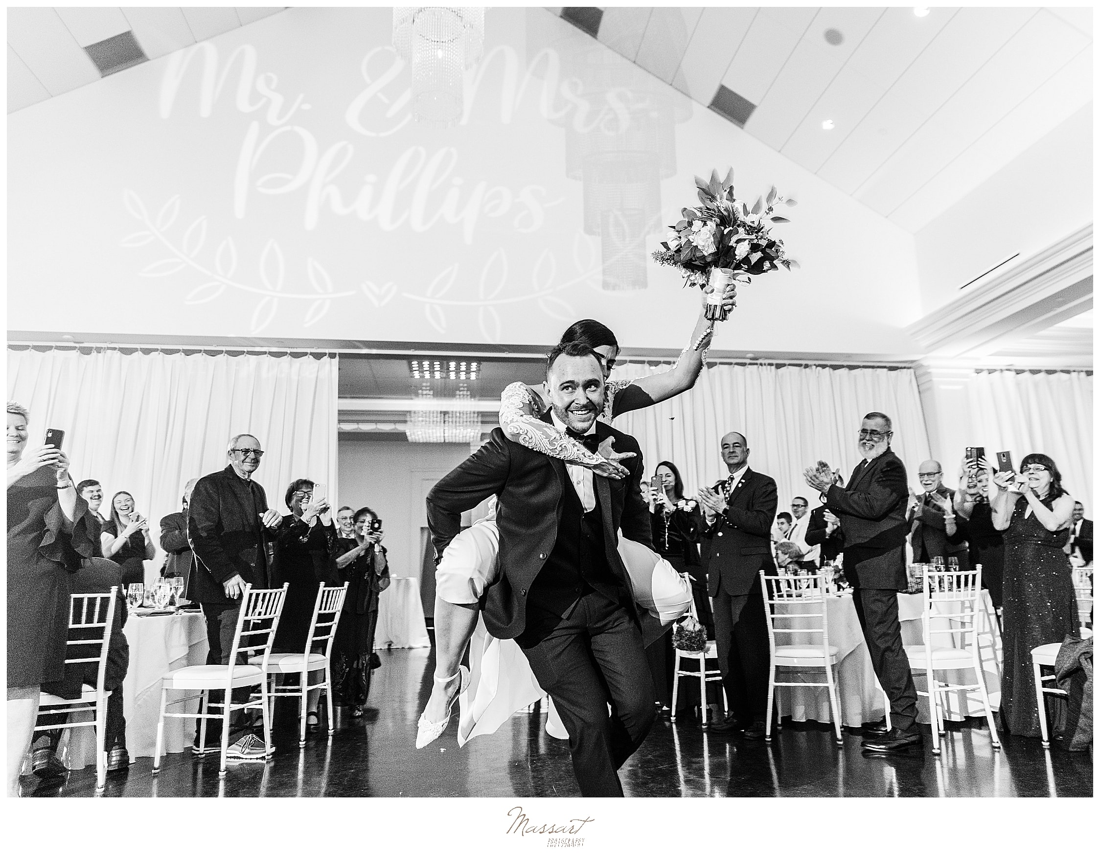 bride and groom enter wedding reception in MA with Massart Photography