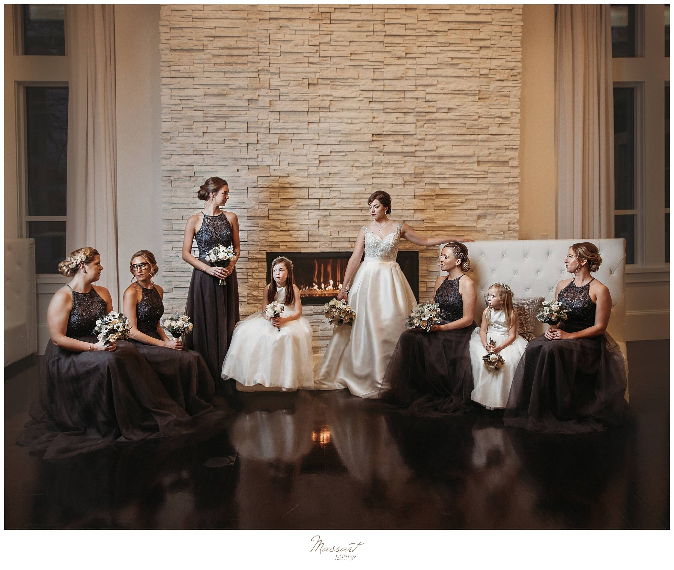 bride with bridal party in grey gowns and 2 flower girls by fireplace photographed by Massart Photography