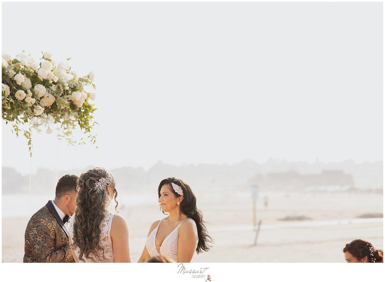 brides hold hands during wedding ceremony