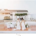 brides pose by arbor for ceremony at Newport Beach House