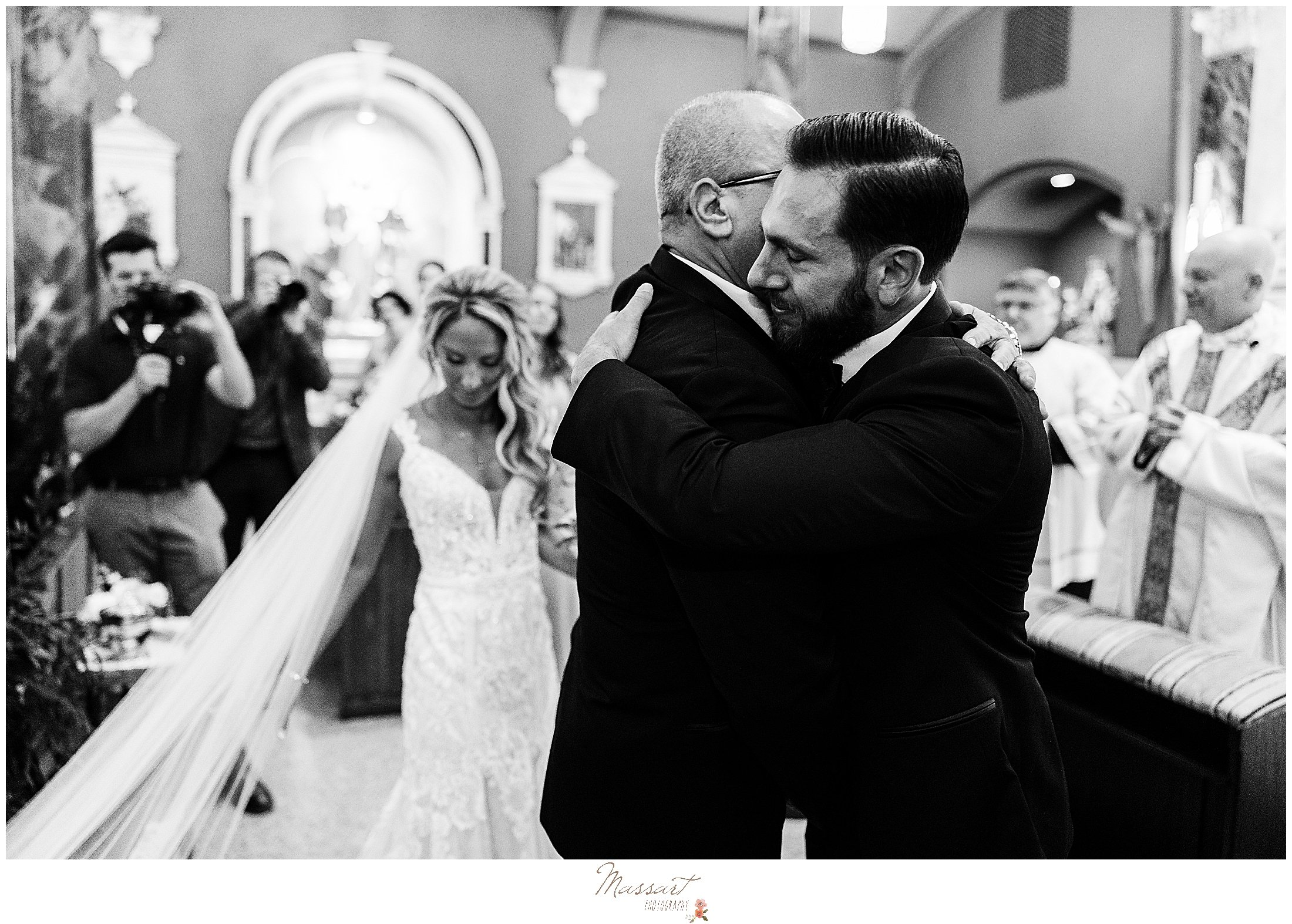 father of bride hugs groom during ceremony at St. Mary's Catholic Church