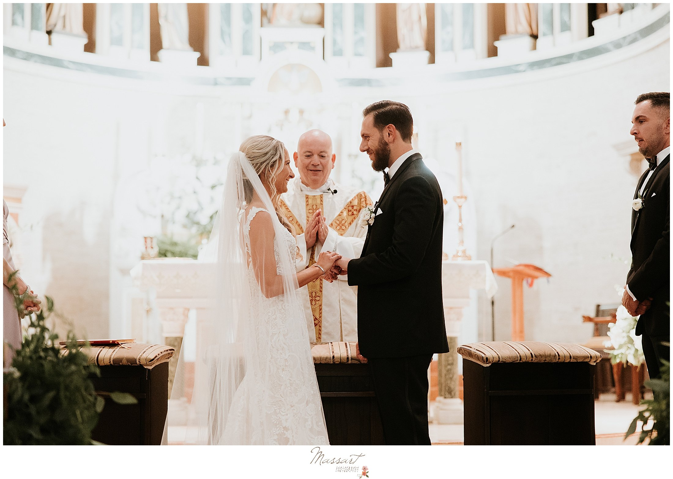 bride and groom exchange vows during traditional church wedding in St. Mary's Catholic Church