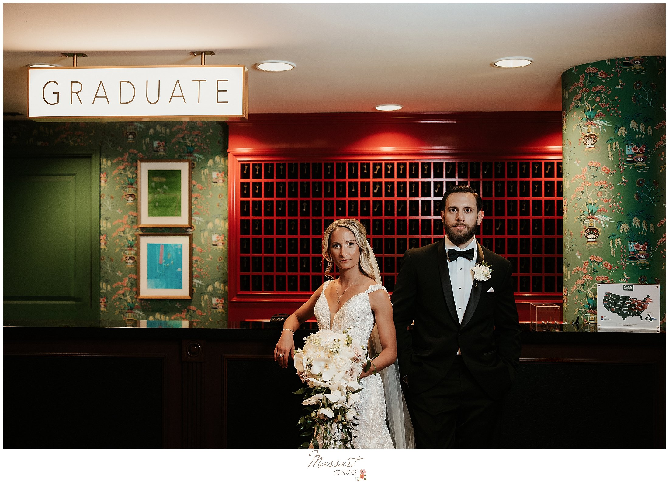 bride and groom pose by front desk before The Graduate Hotel wedding