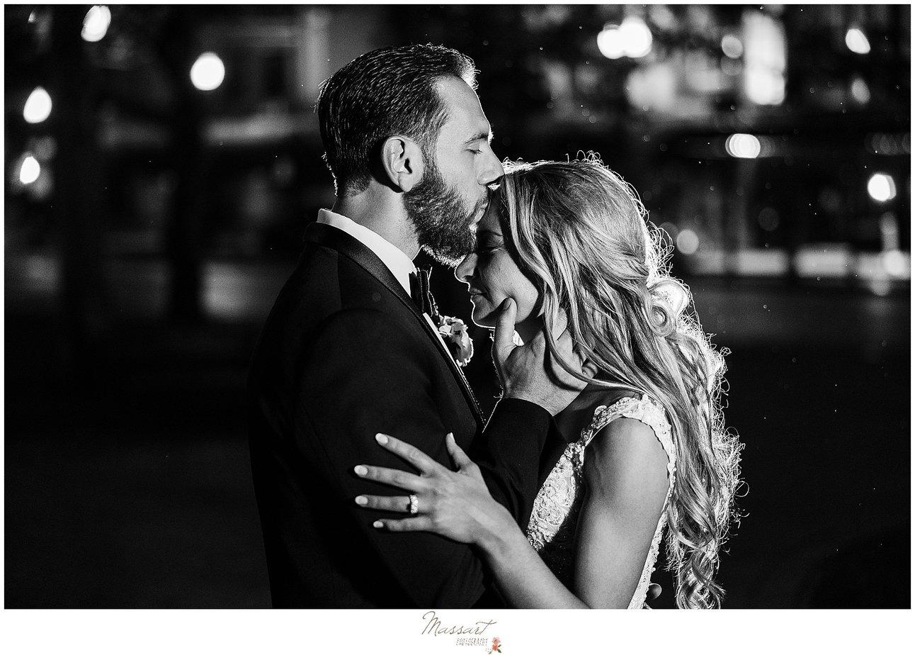 nighttime wedding portraits outside the Graduate Providence of groom kissing bride
