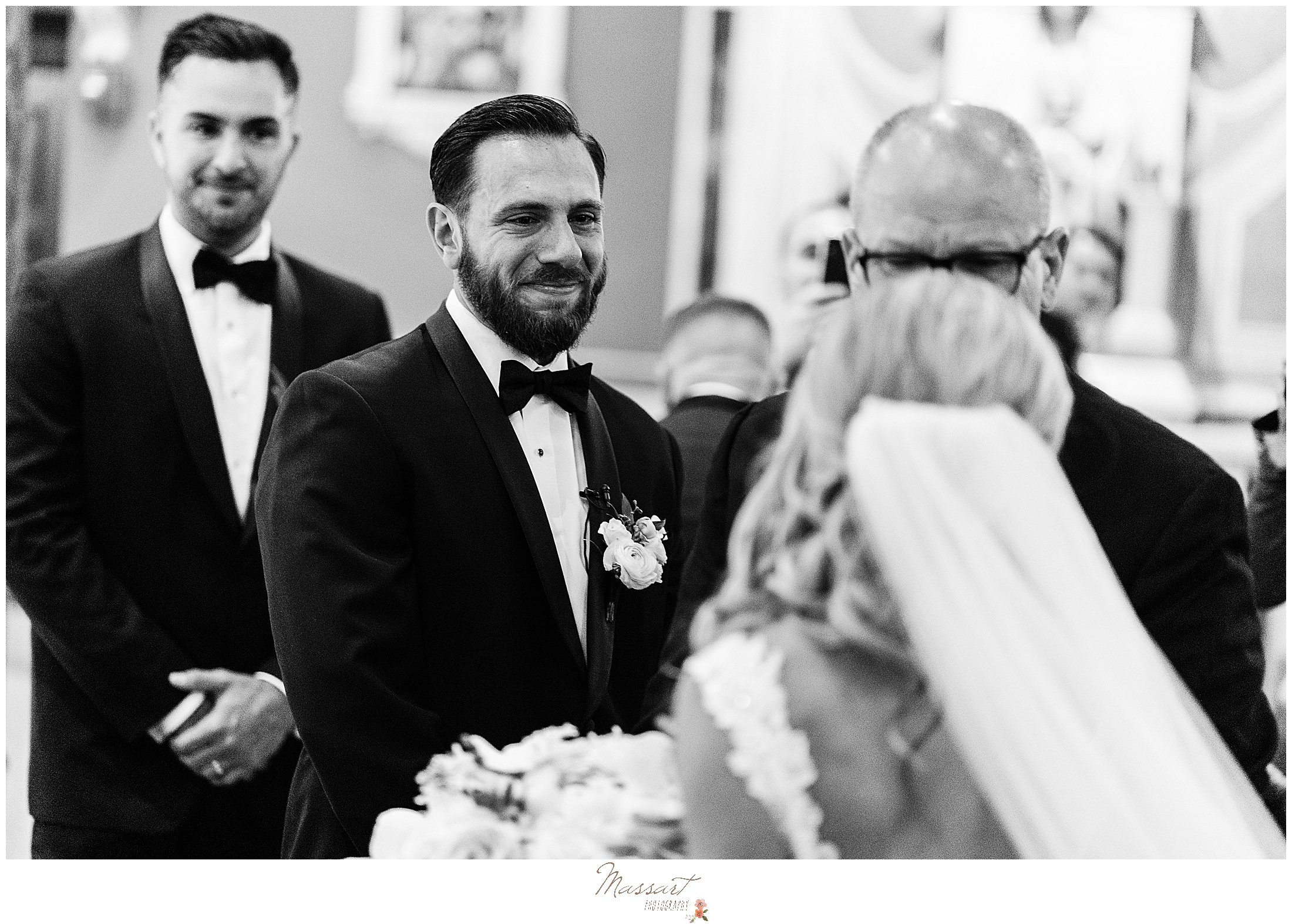 groom looks at bride during wedding ceremony at St. Mary's Catholic Church