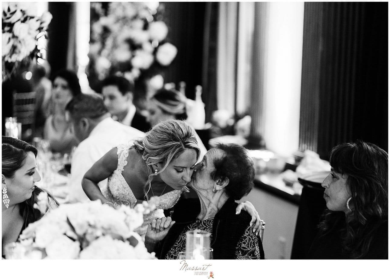 bride kisses grandmother during wedding reception
