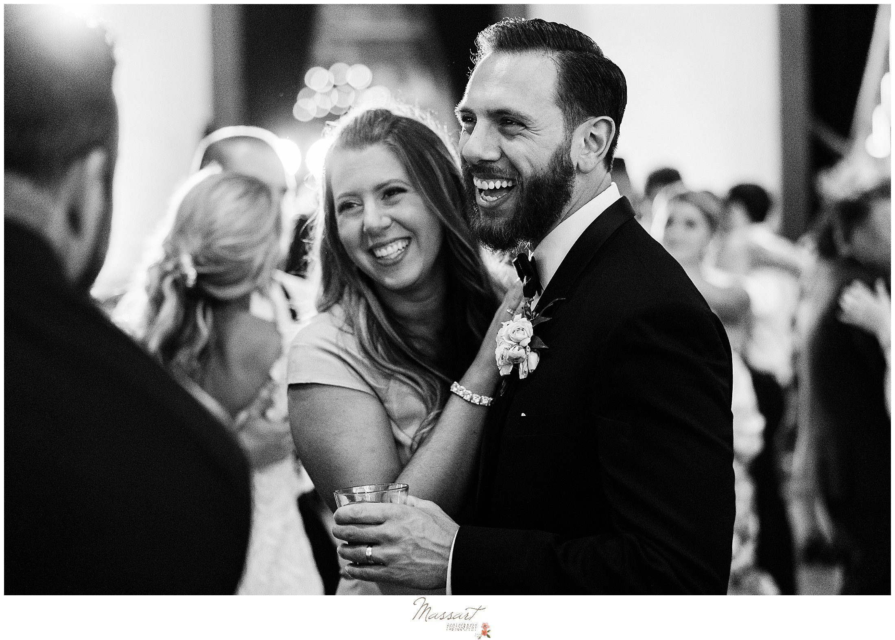 guest hugs groom during wedding reception